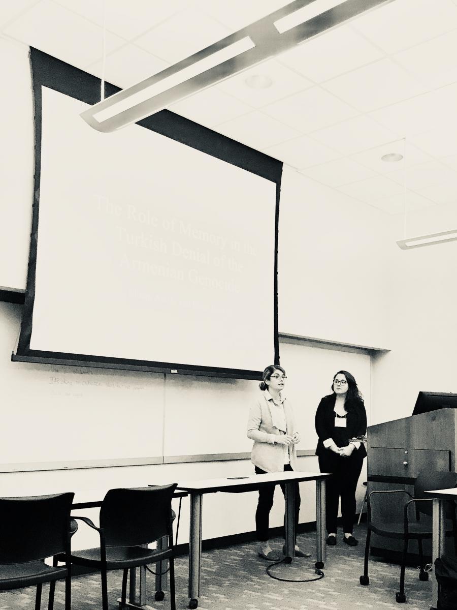 Professor Elham Atashi and student Elena Itamari stand in front of a whiteboard to present